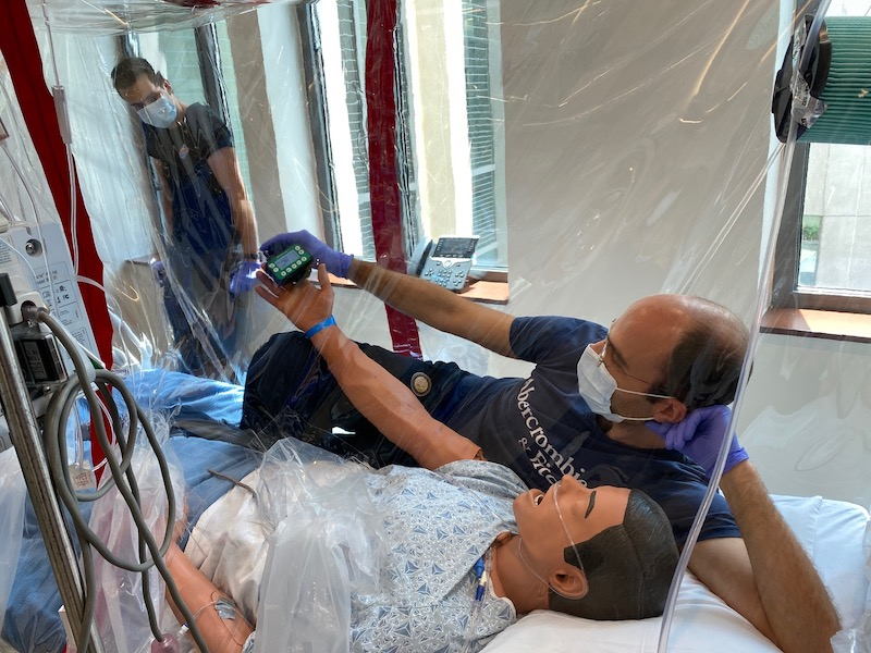 Dr. Economopoulos conducting particulate testing with Air Precision on his isolation tent, COVIAGE. Also pictured is recent BME graduate, Ben Wesorick.